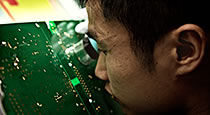 Close-up on person studying a PCB with magnifier